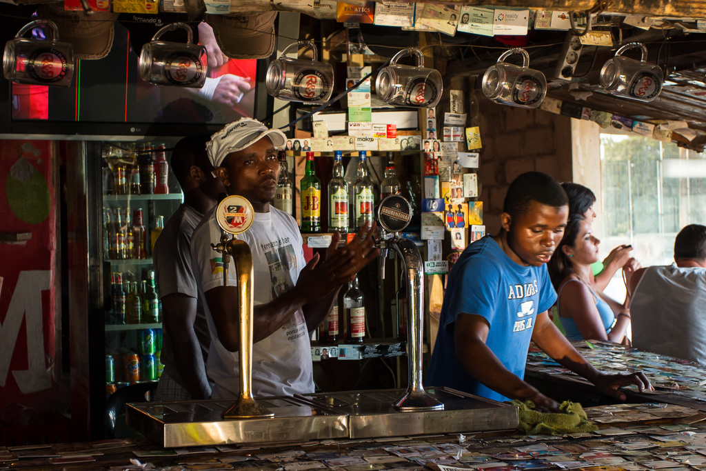 Golden sunset light shines into Fernando's Bar, illuminating the barman's face. Ponta do Ouro, Mozambique