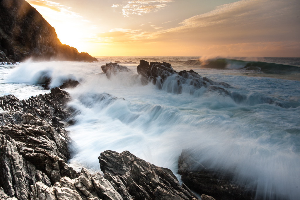 Waves crash on the rocky shoreline at sunrise