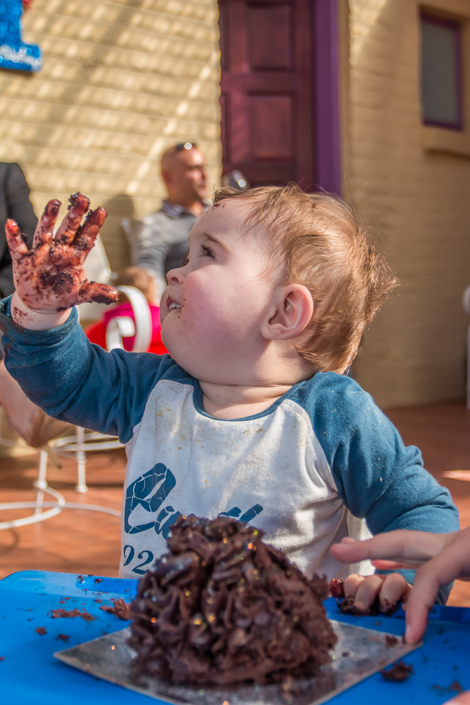 A one year old smashes his birthday cake at his birthday party